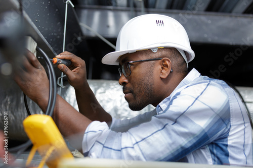electrician fitting a cable for ceiling light - fototapety na wymiar