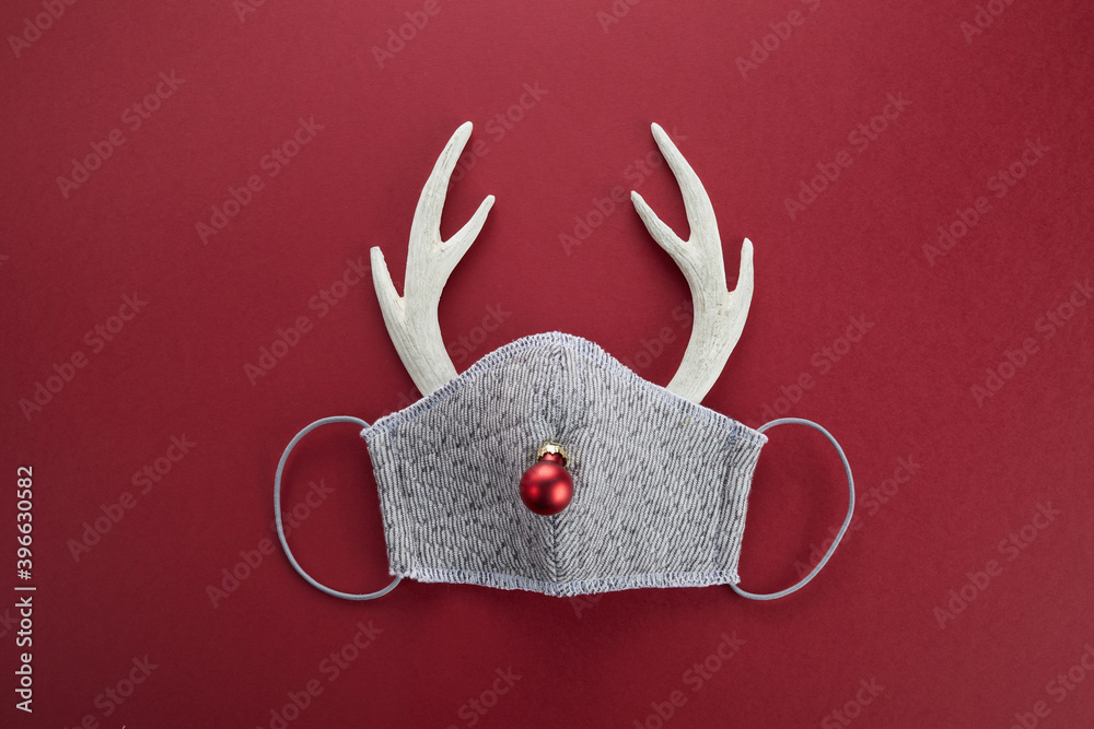 Fototapeta Reindeer horns with face mask and red ball. Pandemic Christmas concept. Flat lay.