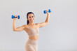 Leinwandbild Motiv Positive sporty woman in beige activewear smiling and posing with dumbbells in studio