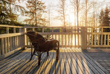 The Armchair Stands On The Veranda Of A House On The Shore Of The Lake In The Rays Of The Setting Sun. Relaxation.