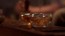 Cozy Atmosphere Of A Tea Room In A Chinese Province. A Stream Of Fragrant Tea From A Porcelain Teapot Fills Two Glass Bowls. Close-up, Warm Light. Slowmo.