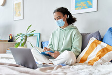 Mixed Race Teenage Girl Wearing Face Mask Remote Studying Online At Home. African Teen Distance Learning Watching Webinar, Virtual School Class With Teacher Using Laptop Studying During Coronavirus.