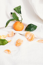 View Of Orange Fruit And Slices On Tablecloth