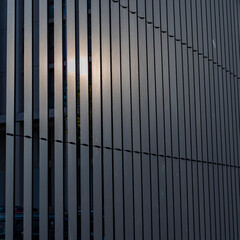 Tall metal fence barrier with sun reflected on it.