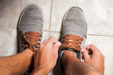 Detail Of The Hands Of A Young Brazilian Man Tying The Tennis Shoe To Practice Walking In The Neighborhood. Footwear Concept. Sport Concept.