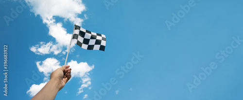 Fototapeta checkered race flag in hand over blue sky obraz