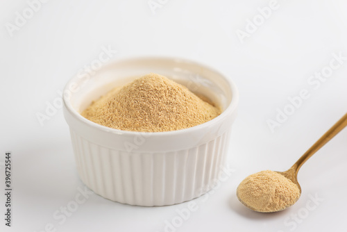 Fotografia, Obraz Lecithin powder in a bowl with a spoon on a white background.