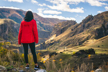 Female Tourist Stands On The Rock And Admires Dramatic Landscape Of Rocky Area In Vardzia With Tmogvi Fortress On Top Hill. Solotravel Adventure Woman.