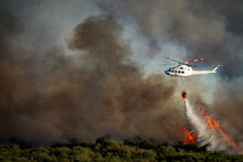 Smoke And Huge Fire And Blurred Helicopter With Bambi Bucket Dumping Water
