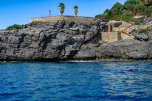 View From The Sea To The Abandoned Park Emirgan Ulas Mesire Yeri In Alanya (Turkey). Two Palm Trees Grow On A Stone Artificial Terrace In A Granite Rock Among Turquoise Water