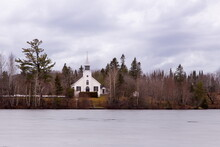 White Catholic Chapel Surrounded By Woods Seen Across A Lake During A Grey Misty Winter Day, Lac-Beauport, Quebec, Canada