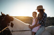Happy mother and daughter riding a horse at sunset - Family and love concept - Focus on kid face