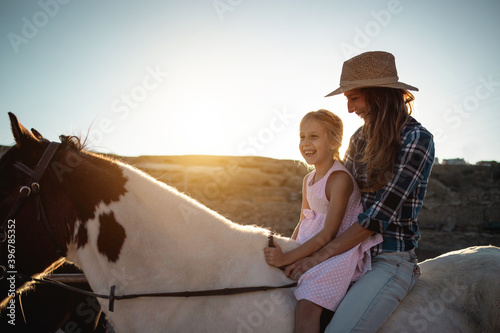 Fototapeta Happy mother and daughter riding a horse at sunset - Family and love concept - Focus on kid face obraz