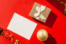 Gold Gift And Blank Form For Congratulations On A Red Background. Flat Lay Style. Christmas Time