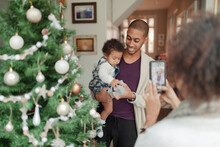 Woman Photographing Husband And Baby Daughter At Christmas Tree