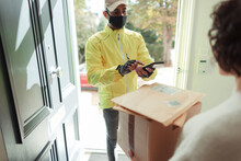 Woman Receiving Packages From Delivery Man In Face Mask At Front Door
