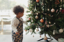 Cute Baby Girl Looking At Christmas Tree Decorations