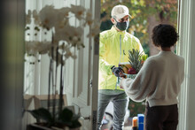 Woman Receiving Grocery Delivery From Courier In Face Mask At Door