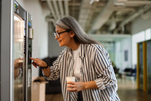 Happy White-haired Woman Using Vending Machine While Drinking Coffee