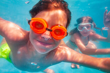 Selfie Portrait Of A Boy In Orange Googles Dive In The Pool With Friends Have Smile On His Face