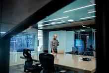 Man Using Phone In Office Meet...