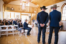 Groom And Best Man In Cowboy Hats Waiting At Altar On Wedding Day