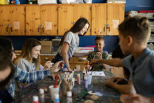 Camp Counselors Teaching Crafts To Boys At Summer Camp