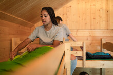 Girl Making Bed In Cabin At Summer Camp