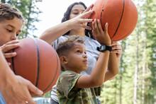 Camp Counselor Teaching Boys Basketball At Summer Camp