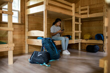 Girl Using Phone In Dormitory Cabin At Summer Camp