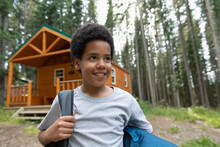 Boy With Backpack Standing In Front Of Cabin At Summer Camp