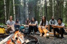 Children Sitting Around Campfire In Summer Camp