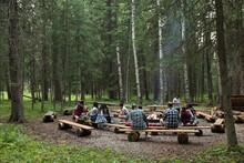 Children Sitting In Forest Summer Camp