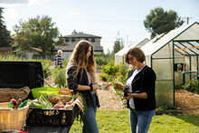 Woman Paying Friend For Vegetables In Community Garden