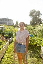 Girl With Rake And Spade In Community Garden