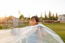 Volunteer Preparing Netting In Community Garden