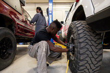 Auto Mechanic Changing Custom Tire On Lifted SUV In Garage