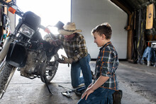 Grandfather And Grandson Fixing Motorcycle In Barn