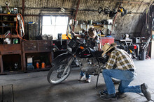 Grandfather And Grandson Fixing Motorcycle In Barn Workshop