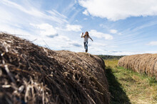 Carefree Girl Running And Playing On Rolled Hay Bales On Sunny Farm