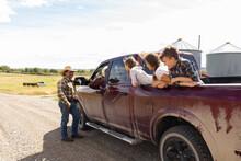 Farmer Family In Pickup Truck On Sunny Rural Farm