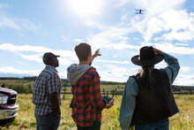 Male Ranchers Operating Drone In Sunny Field On Rural Ranch
