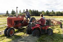 Male Farmers Talking On Tractors In Sunny Rural Field
