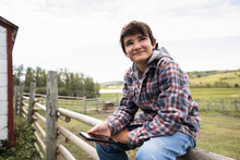 Portrait Confident Happy Boy With Smart Phone On Farm Fence