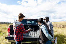 Male Ranchers Preparing Drone At Back Of Pickup Truck In Sunny Field
