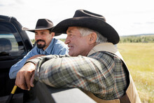 Father And Son Farmers In Cowboy Hats At Pickup Truck On Sunny Farm
