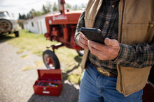 Close Up Senior Male Farmer Using Smart Phone By Tractor