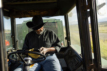 Senior Male Farmer Using Smart Phone Inside Tractor In Sunny Field