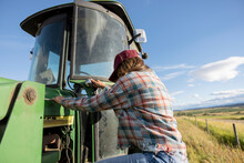 Female Farmer Climbing Up Into Tractor In Sunny Rural Farm Field
