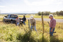 Ranchers Building Barbed Wire Fence In Grass On Sunny Rural Ranch